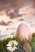 Large pink egg with daisies in tall grass