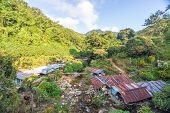 stock photo of shacks  - Rustic shacks in a beautiful valley in the Sierra Nevada de Santa Marta in Colombia - JPG