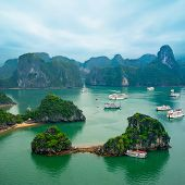 Tourist Junks Floating Among Limestone Rocks At Early Morning In Ha Long Bay, Vietnam