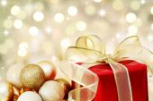 stock photo of christmas party  - Red Christmas gift box and baubles on background of defocused golden lights - JPG
