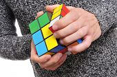 TARRAGONA, SPAIN - FEBRUARY 3, 2014: A man trying to solve a Rubiks cube. This famous cube puzzle wa