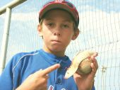 Young Baseball Player holding a Ball w/ the Leather