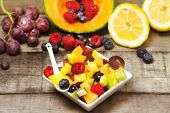 stock photo of greedy  - greedy fruit salad with red fruits and fruits background on wood - JPG