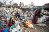 KATHMANDU, NEPAL - DEC 19, 2013: Unidentified child is sitting while her parents are working on dump