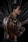 Art. Young attractive retro model in old-fashioned wild clothing Tribe. Tattoo. Native savage man