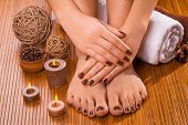 beautiful brown manicure and pedicure on bamboo background