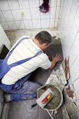 Tiler At Work Bonding Of Floor  Tile Adhesive
