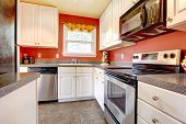 image of concrete  - Small kitchen room with concrete tile floor red walls steel appliances and white wooden cabinets - JPG