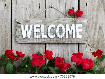 Rustic Welcome Sign Hanging On Wood Fence With Flower Border Of Red Roses Picture