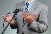Businessman making speech with microphone and hand gesturing concept for explaining, protesting or b
