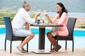 Man and girl drinking wine at street cafe on a date with flover on table