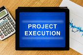 foto of execution  - project execution word on digital tablet with calculator and financial graph - JPG