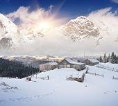 Winter landscape with mountain villages. Wooden houses on a snowy meadow. Carpathian mountains, Ukra