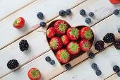 Fresh Strawberries And Blueberries In Hearth Shape Basket On Kitchen Table