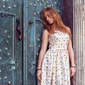 Fashion Red-haired Girl Standing Near A Blue Wall