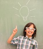 Smart schoolboy on school board with bulb for idea