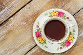 Tea in vintage cup on wooden surface