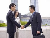 picture of rep  - asian business people shaking hands with urban background - JPG