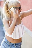 Blonde teen girl talking on the phone outdoor