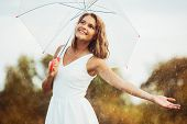 Portrait of beautiful young girl walking with umbrella under rain