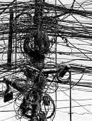 Electric wires on a post in Kathmandu, Nepal in black and white