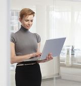 Young attractive elegant caucasian businesswoman standing with laptop computer at office. Working, l