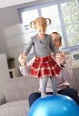 Little girl balancing on fit ball at home in living room, father helping by holding hands.