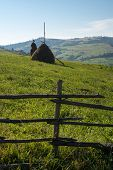 Wooden Fence, Haystacks And White Stork In The Ukrainian Carpathians