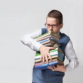 Schoolboy in glasses with books