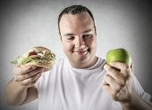 chubby man deciding whether to eat an apple or a hamburger