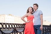 Young Man And Woman Stand Together At The City Embankment Confidently Looking Forward