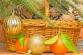 Christmas Balls And Tangerines On A Background Of A Basket With Pine Cones