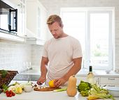 stock photo of single man  - Handsome young man cooking at home preparing salad in kitchen - JPG