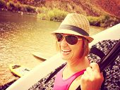 a pretty woman carrying a surf board or stand up paddle board down to the river on a hot summer day toned with a retro vintage instagram filter effect