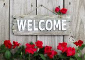 Rustic welcome sign hanging on wood fence with flower border of red roses