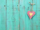 Red checkered and gold hearts hanging from rope on antique teal blue wood background