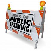 Fear of Public Speaking words on a road construction barrier or barricade illustrating anxiety or st