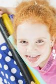 Funny Red-haired Caucasian Girl Making Faces. Against White