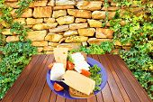 savory set of cheese greek goat feta yellow fromage french on blue plate over wooden table at outdoo
