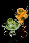 Two Fresh Orange and lime Mojito over black  background