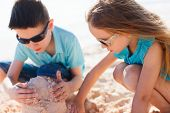 Brother and sister playing with sand at tropical beach