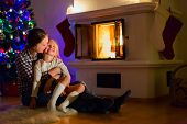 Mother and daughter sitting by a fireplace in their family home on Christmas eve