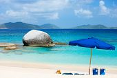 Picture perfect beach with blue umbrella, white sand and turquoise ocean water at tropical island in