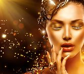 Beautiful Magic Woman Portrait. Golden Makeup. Model Girl face with gold skin, nails, make-up and ac