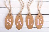 Sale tags on white wooden background