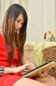 Beautiful Woman In Red Dress Resting On A Sofa While Playing With A Tablet In Living Room