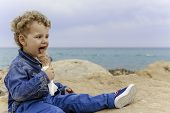 Постер, плакат: Child Eating An Ice Cream On The Beach