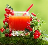 Berry juice and forest cowberry with leaves against blurred green background.