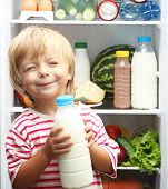Happy little boy with milk against refrigerator with food