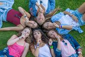 group of teens girls  fingers to lips for surprise secret.